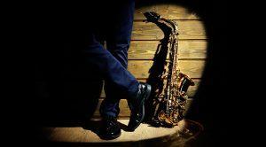 Saxofón alto al lado de unas pierna